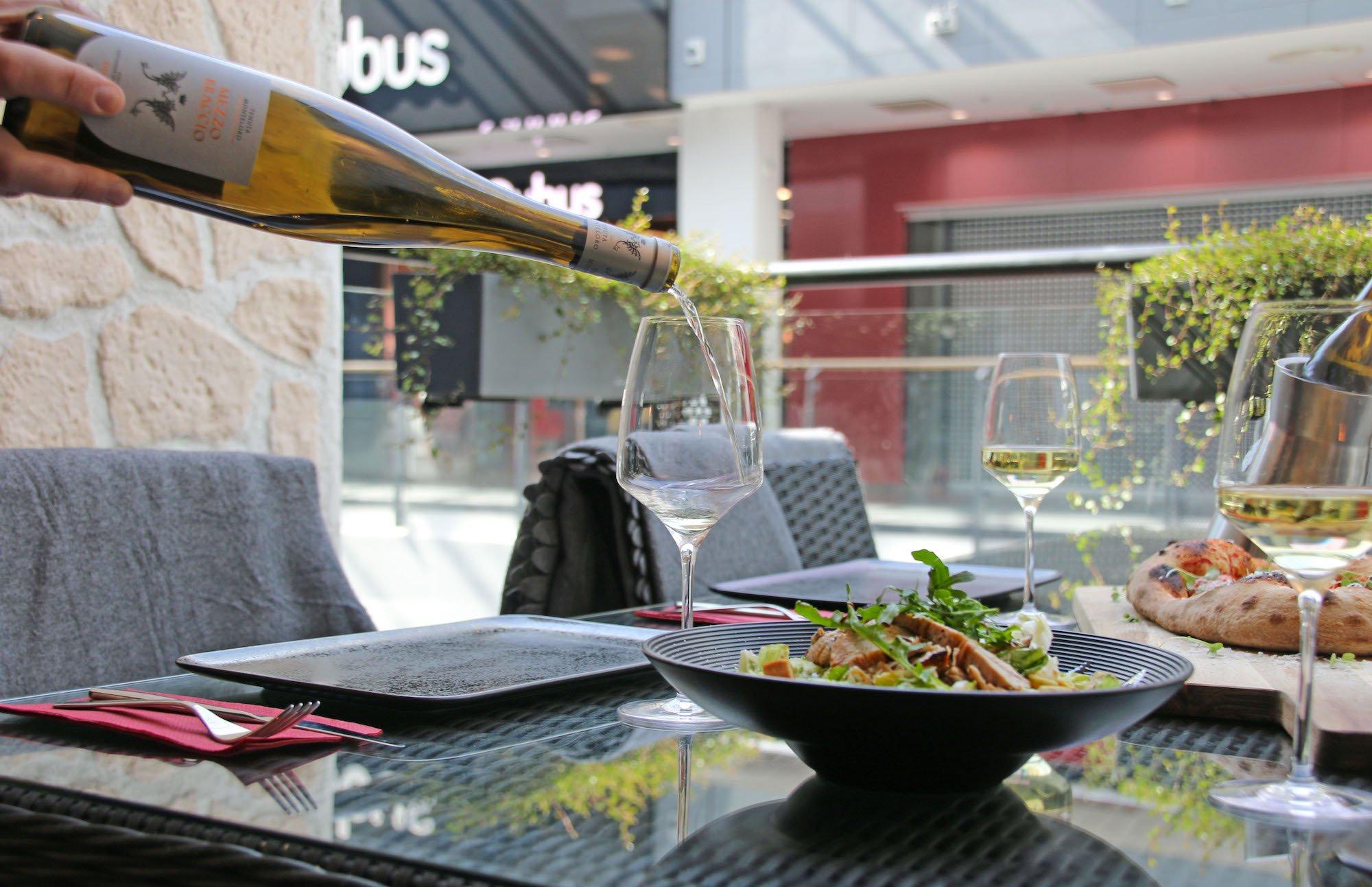 Salaatti RAK Edge lautasella ja valkoviiniä